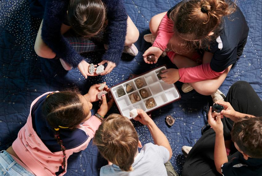 Group of children sitting in a circle looking at rock specimens