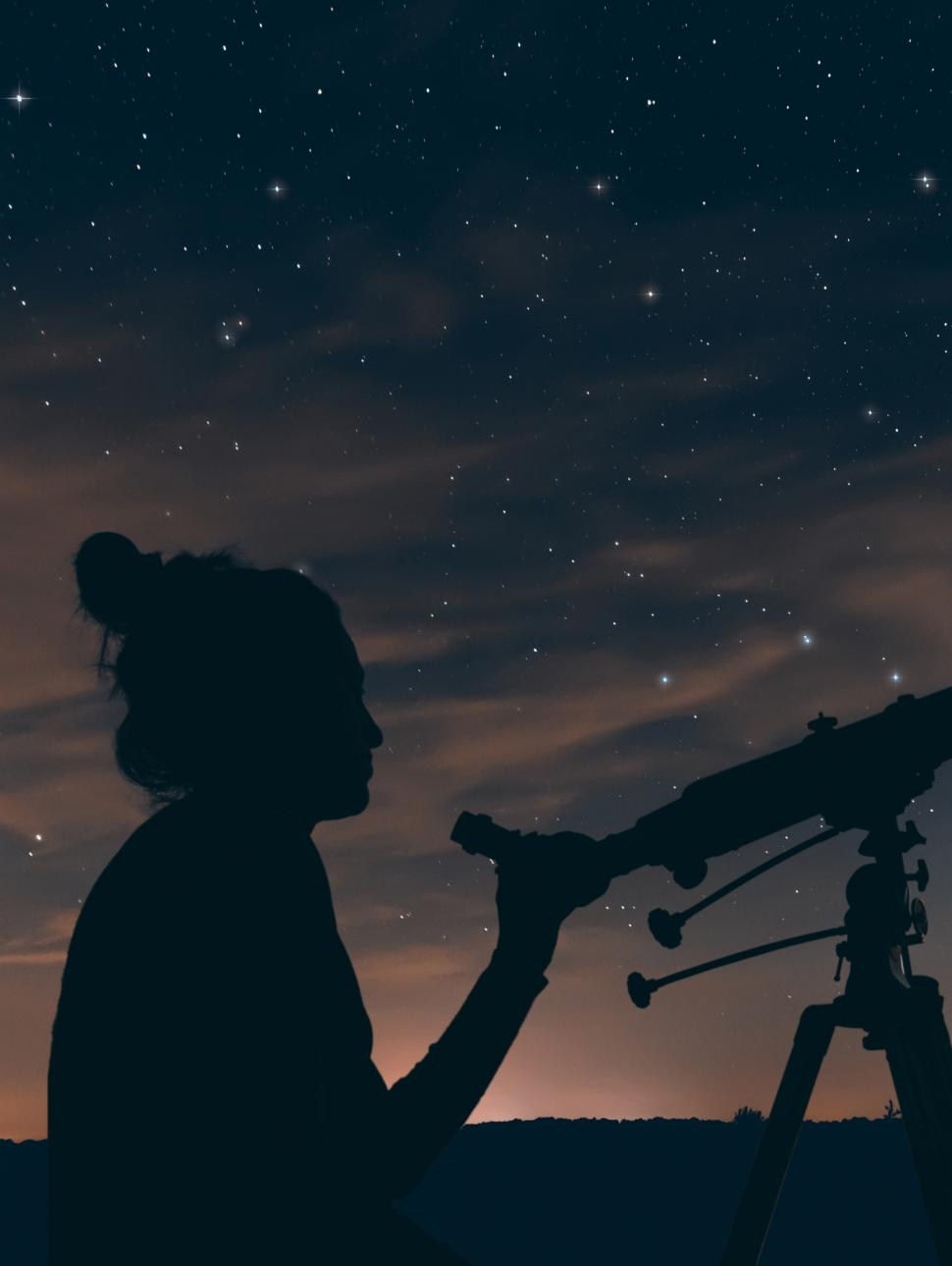 A person holding a telescope is silhouetted against an evening sky