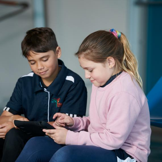 Two young children sitting and looking at an ipad