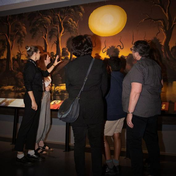 A group of people stand together with a tour guide, examining a large artwork in a museum gallery