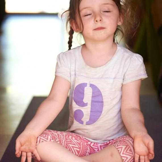Little girl seating in a yoga position