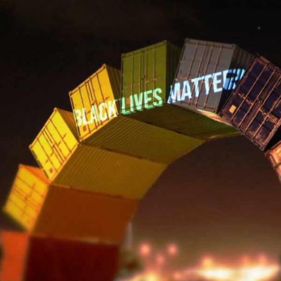 A rainbow of painted shipping containers with 'Black Lives Matter' projected at the top of the arc