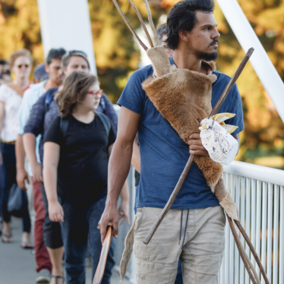 Several people are walking across a bridge towards the camera; the serious-looking man at the front is holding some wooden tools or weapons wrapped in an animal skin
